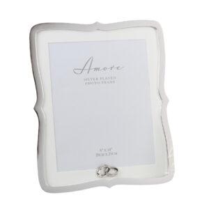 Gyönyörű, ezüstözött fésűkagyló képkeret, kristály gyűrűkkel, az AMORE BY JULIANA® Nagy Nap kollekciójából. A keret összefonódó ezüstözött kristály gyűrűkkel, törtfehér paszpartuval és támasszal rendelkezik.
